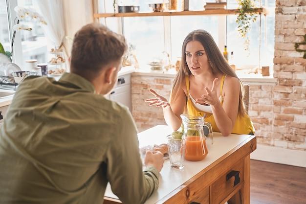 논쟁하지 마십시오. 감정적인 젊은 여성은 남자친구와 이야기하면서 적극적으로 몸짓을 합니다. 국내 컨셉