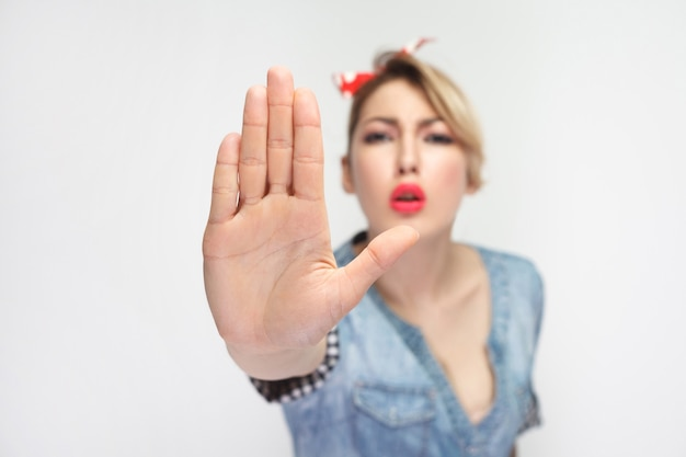 Не подходи ко мне. портрет серьезной красивой молодой женщины в повседневной голубой джинсовой рубашке с красной повязкой на голову, стоящей и смотрящей в камеру с жестом остановки. студия выстрел, изолированные на белом фоне.