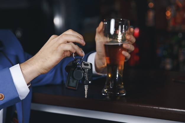 車のキーを話している飲酒運転のトリミングされた画像を飲んだり運転したりしないでください