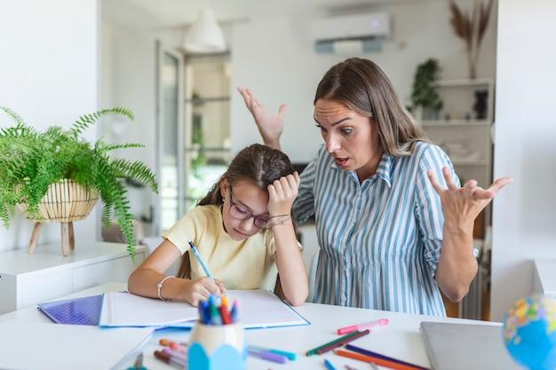 私が話しているときに私を無視しないでください。宿題を手伝っているお母さん。娘が宿題をしたくないので、お母さんは怒っています。ストレスのたまった母と娘は、宿題の失敗に不満を感じていました。