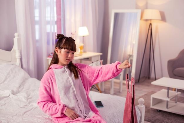 Не нравится. сосредоточенная брюнетка школьница сидит на своей кровати и выбирает необходимое платье