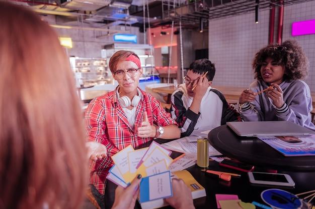 Не нравится. негативная восторженная международная девушка, опершись локтями о стол во время разговора о проекте