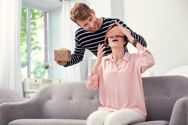 Не смотреть. хороший радостный мужчина, закрывая глаза матери, готовя ей подарок