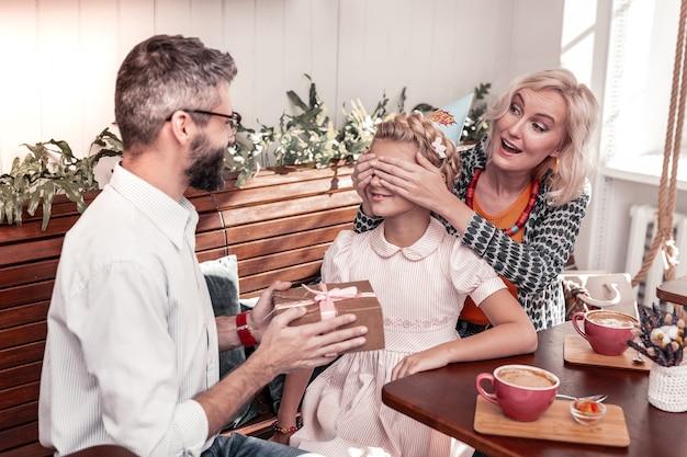 보지 마십시오. 그녀를 위해 선물을 준비하는 동안 그녀의 딸의 눈을 덮고 즐거운 젊은 여자