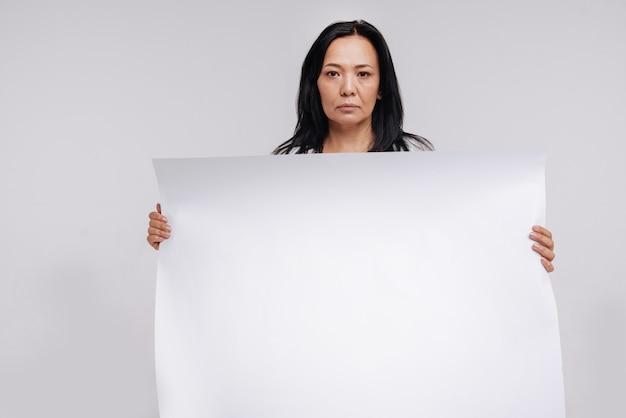 Не пропустите этот знак. амбициозная сильная современная дама держит пустой плакат, стоя и выражая разочарование