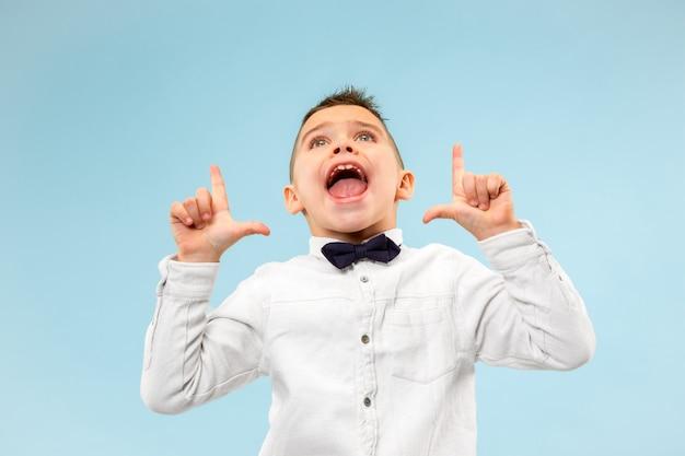 お見逃しなく。カジュアルな少年が叫んでいます。叫び。ブルースタジオの背景に叫んで感情的な10代を泣いています。男性の半身像。人間の感情、表情のコンセプト。流行色