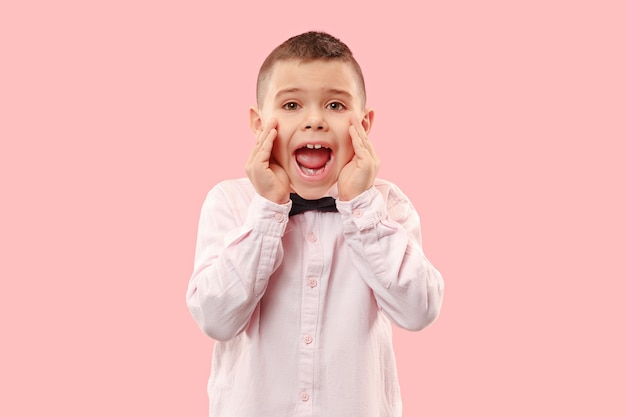 お見逃しなく。叫んでいる若いカジュアルな男の子。叫ぶ。ピンクのスタジオの背景で叫んで泣いている感情的なティーン。男性の半身像。人間の感情、顔の表情の概念。トレンディな色