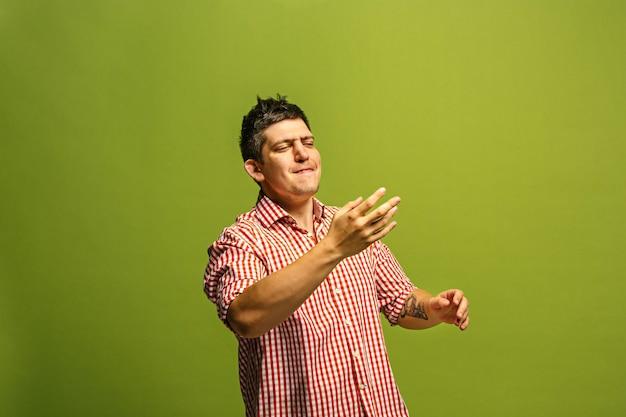 놓치지 마세요. 젊은 캐주얼 남자 소리. 외침. 녹색 스튜디오 배경에 비명 감정적 인 남자 울고. 남성 절반 길이 초상화.