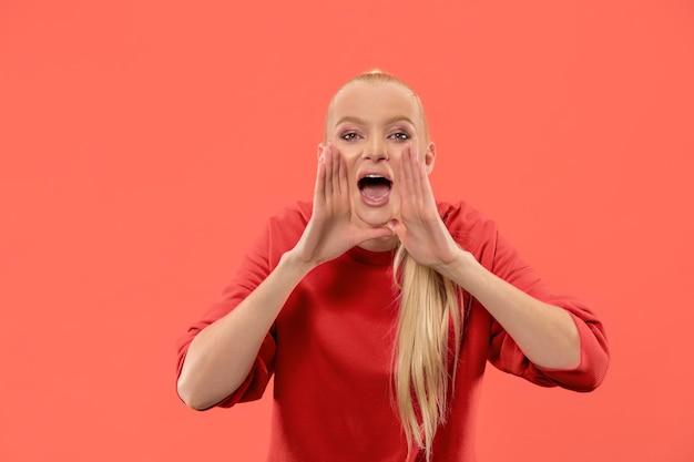 お見逃しなく。若いカジュアルな女性が叫んでいます。叫ぶ。珊瑚スタジオの背景で叫んで泣いている感情的な女性。女性の半身像。人間の感情、顔の表情の概念。トレンディな色
