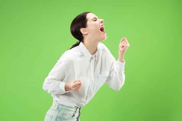 お見逃しなく。若いカジュアルな女性が叫んでいます。叫ぶ。緑地で叫んで泣いている感情的な女性。女性の半身像