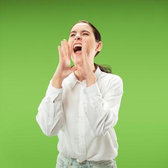 お見逃しなく。若いカジュアルな女性が叫んでいます。叫ぶ。緑のスタジオの背景で叫んで泣いている感情的な女性。女性の半身像。人間の感情、表情の概念。トレンディな色