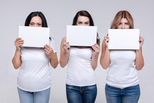 Не выключайте нас. различные симпатичные и решительные женщины держат белые таблички, закрывающие половину лица