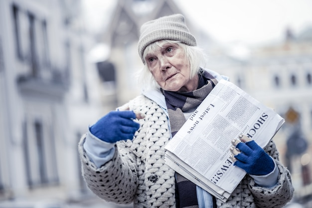 通り過ぎないでください。通りに立って新聞を売る悲しい真面目な女性