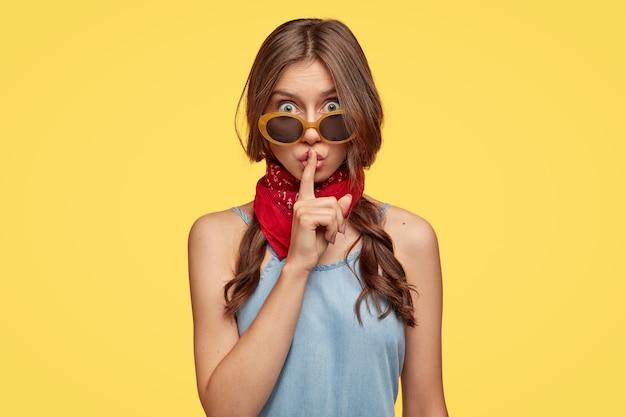 이 정보를 누구에게도 말하지 마십시오. 매력적인 여성은 두 개의 주름을 가지고 있고, 쉿쉿 한 몸짓을하고, 조용하고 침묵을 요구하고, 선글라스를 착용하고, 세련된 복장을하고, 노란색 벽 위에 실내 모델을 착용합니다.