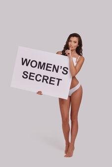 誰にも言わないでください。ポスターを保持し、灰色の背景に立っている間、彼女の唇で人差し指を保持している魅力的な若い女性の全長