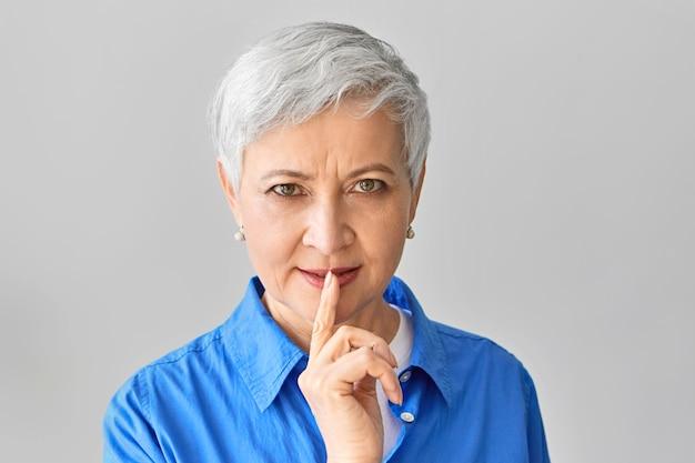 誰にも言わないでください。灰色のシャツの髪を唇に人差し指で抱きかかえ、身をかがめ、孫に秘密を守るように頼む、神秘的な遊び心のある祖母。静かな、要求の厳しい成熟した女性