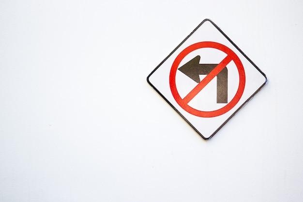 空の白い壁に取り付けられた「左折しないでください」の標識。左側のスペースをコピーします。