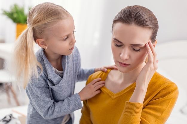 動揺しないでください。彼女と母親がこめかみに触れることを心配しながらお母さんの肩に手を置く甘いかわいいブロンドの女の子