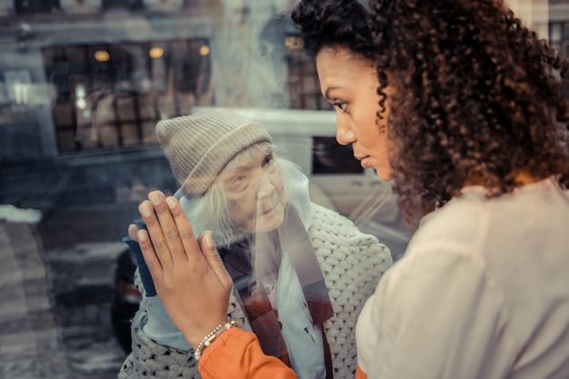 心配しないでください。彼女を助けることを約束しながら年老いたホームレスの女性を見ている素敵な美しい若い女性