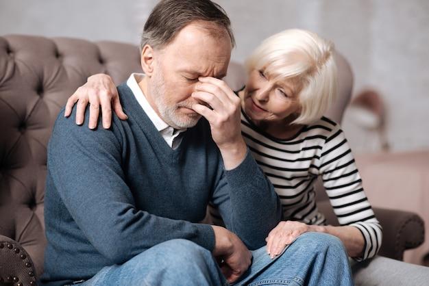 Не беспокойся. старшая дама обнимает своего подавленного мужа, сидя на диване у себя дома.