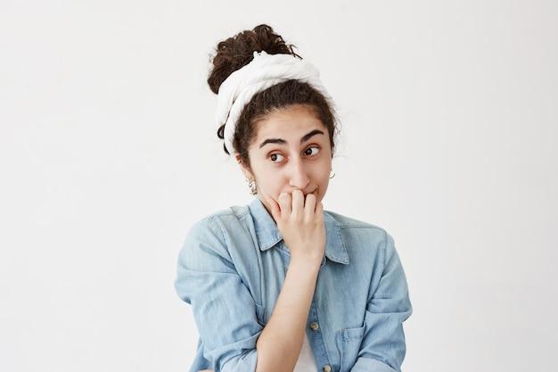 Do-ragとデニムのシャツが暗くて困惑している女性は、混乱したり心配したりして動揺し、指の爪を噛み、困難な状況で抜け出せない、白い壁にポーズをとる