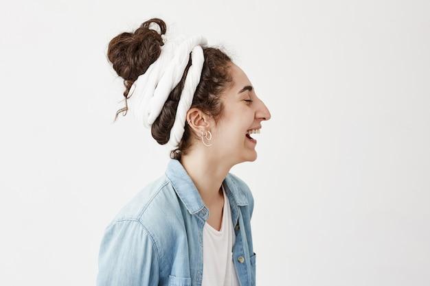 気分が良く、笑顔で笑っているdo-ragの黒くてウェーブのかかった髪の女の子のプロフィール。幸せな笑顔で、夢を見て、良い一日を楽しんでいるきれいな女性。感情と表情