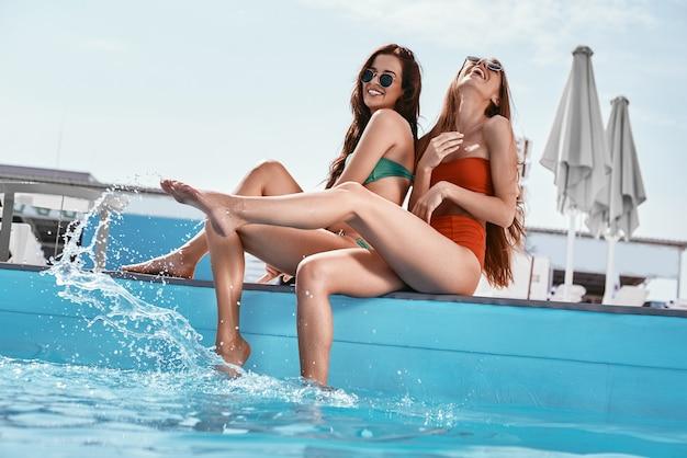 水をはねかけるプールのそばに座っているあなたの夏の女の子と何かクールなことをしてください