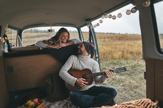내 새 노래 좋아하니? 레트로 스타일의 미니 밴에 앉아있는 동안 그의 아름다운 여자 친구를 위해 기타를 연주하는 잘 생긴 젊은 남자