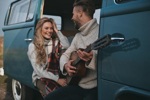 Тебе нравится эта песня? красивый молодой человек играет на гитаре для своей красивой подруги, сидя в синем мини-фургоне в стиле ретро