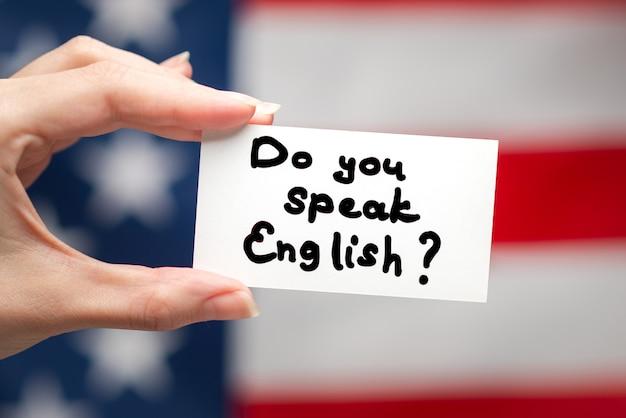 Вы говорите по-английски с текстом на карточке. фон американского флага.