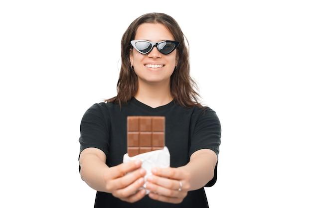 Хочешь немного. довольно молодая женщина держит и дает в камеру плитку шоколада.