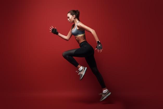 Сделайте свою лучшую спортсменку, прыгающую через красный фон изолированы