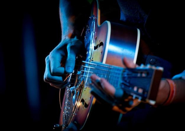 Добро гитара руками во время игры в живом концерте, синий, коричневый цвета