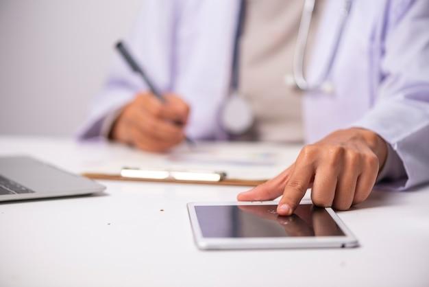 ホワイトテーブル、ヘルスケアコンセプトのドクターと聴診器