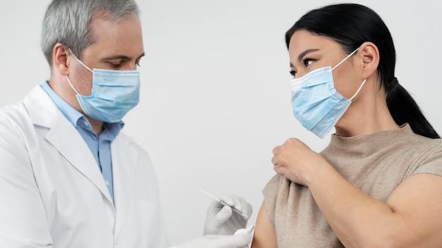 Врач вводит вакцину пациенту женского пола