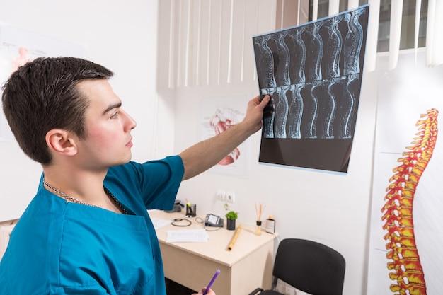Врач анализирует рентгеновское изображение позвоночника человека