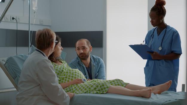 医者とアフリカ系アメリカ人の看護師が子供を期待している女性に相談する