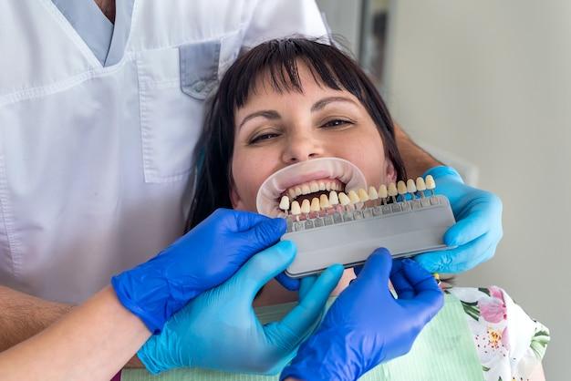 환자의 치아를 샘플러와 비교하는 의사 및 조수