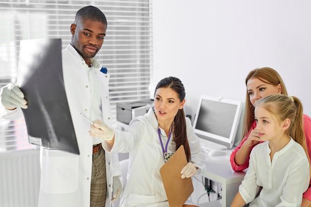 病気の患者に背中のx線写真を見せ、何をすべきか、背中の湾曲、脊柱側弯症を治療する方法を説明する医師と助手