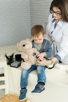 병원에서 테디 베어를 검사하는 의사와 소년 환자