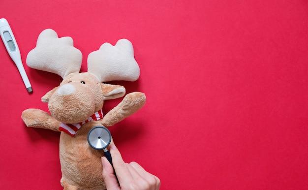 医者とクリスマスのコンセプト。バックは風邪をひく、医師は赤の聴診器で彼をチェックする