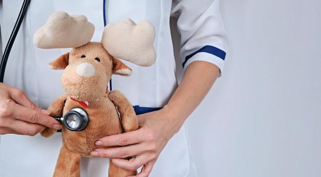 医者とクリスマスのコンセプト。病気の鹿、聴診器で彼をチェックする医者。