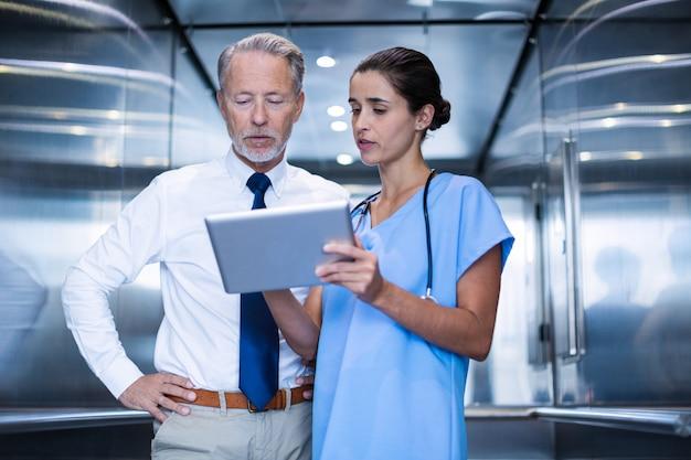 Доктор и коллега обсуждают на цифровой планшет