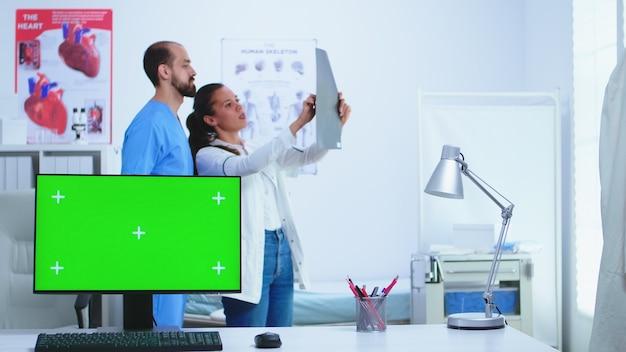 의사와 그녀의 조수는 병원에서 환자 엑스레이와 컴퓨터에 녹색 디스플레이를 확인합니다. 의사가 진단을 위해 환자 방사선 사진을 확인하는 동안 의료 클리닉에서 교체 가능한 화면이 있는 데스크탑