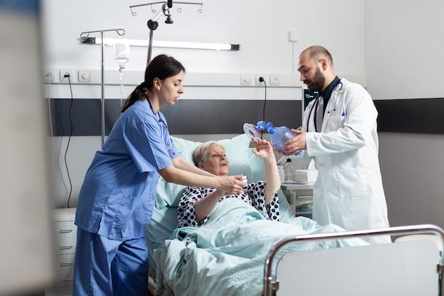 의사와 의료 간호사는 환자의 환기를 위해 인공 호흡기와 호흡 마스크를 사용하여 병실에서 노인 여성의 호흡을 돕기 위해 서두르고 있습니다.