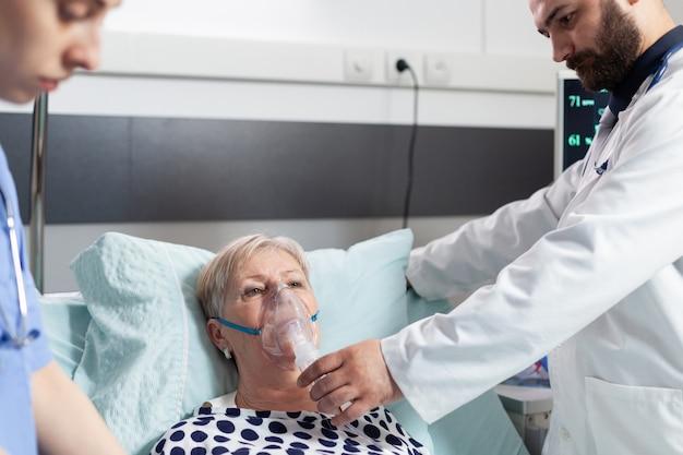 의사와 간호사가 폐 질환으로 인해 침대에 누워 산소 마스크로 호흡하는 고위 여성을 감독합니다.