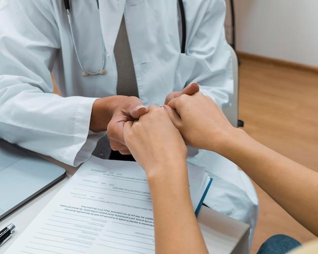 悪いニュースのクローズアップの後に手をつないでいる医師と患者
