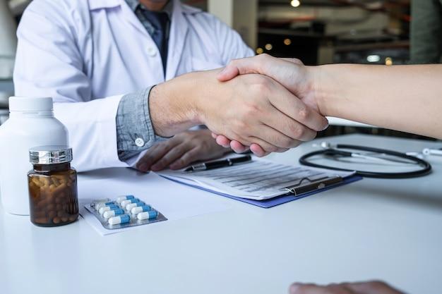 Врач и пациент, пожимая руки после хорошего и успешного лечения в больнице