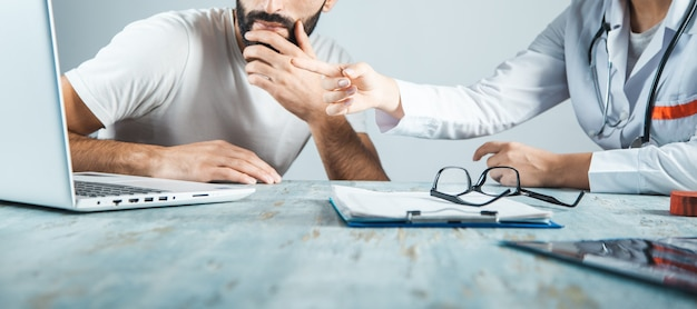 ノートパソコンを見ながら話している医師と患者