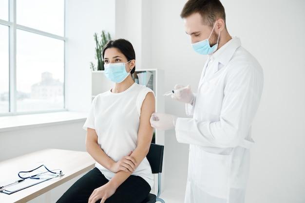 의사와 의료 마스크를 착용하는 환자 covid-19 주사 예방 접종 감염 전염병.